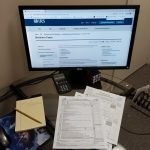 Business tax forms on a glass desk. A computer monitor shows 1120 tax information