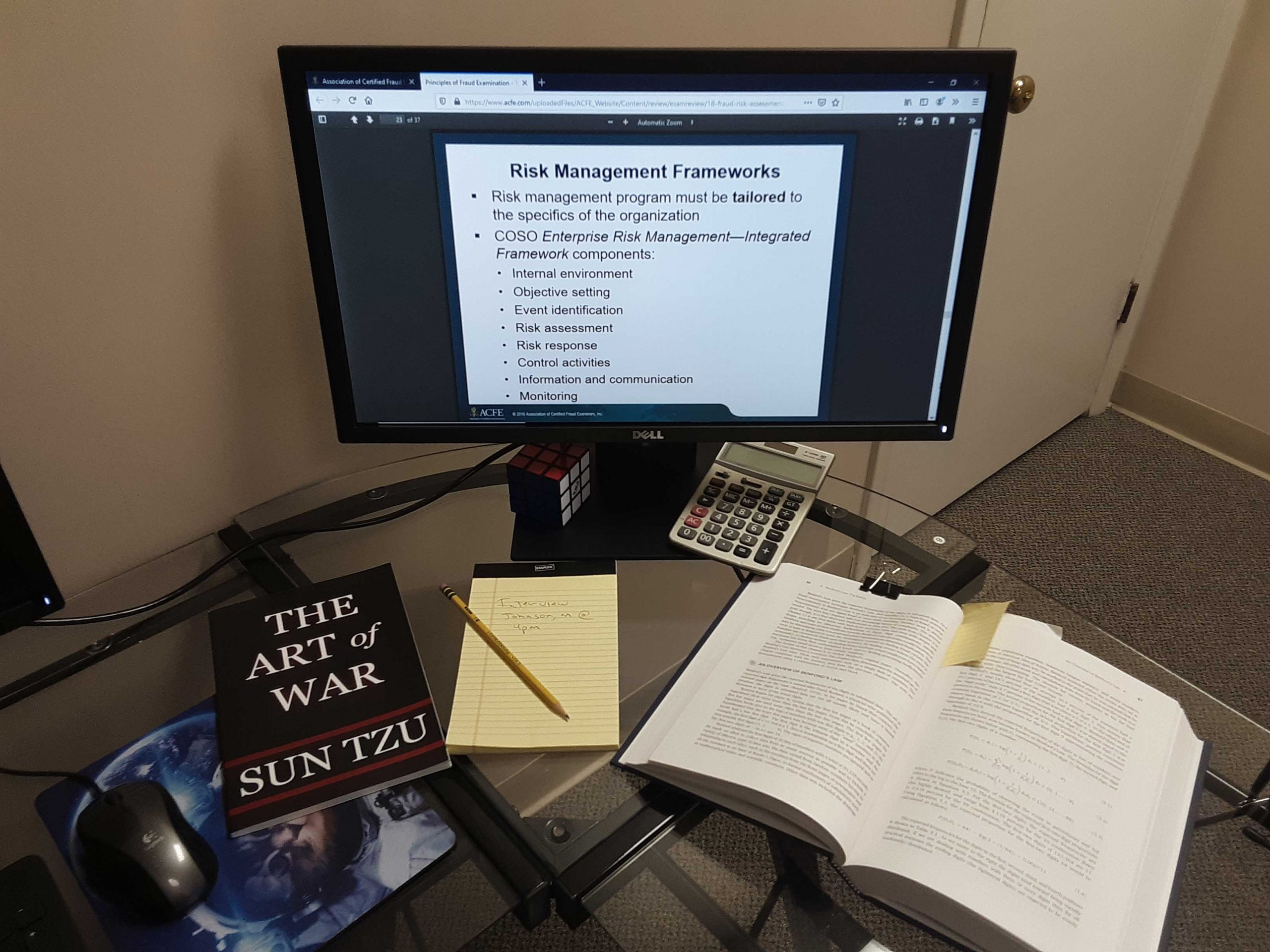 Fraud prevention manual open on a glass desk. A computer monitor in the background with fraud website and the book The Art of War sits to the side.
