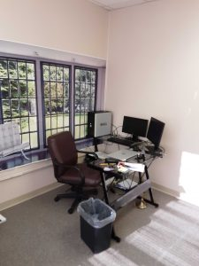 Interior office of Ernest Tomkiewicz CPA PLLC with glass desk and PC with dual monitors