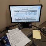 Personal tax forms on a glass desk. A computer monitor shows 1040 tax information